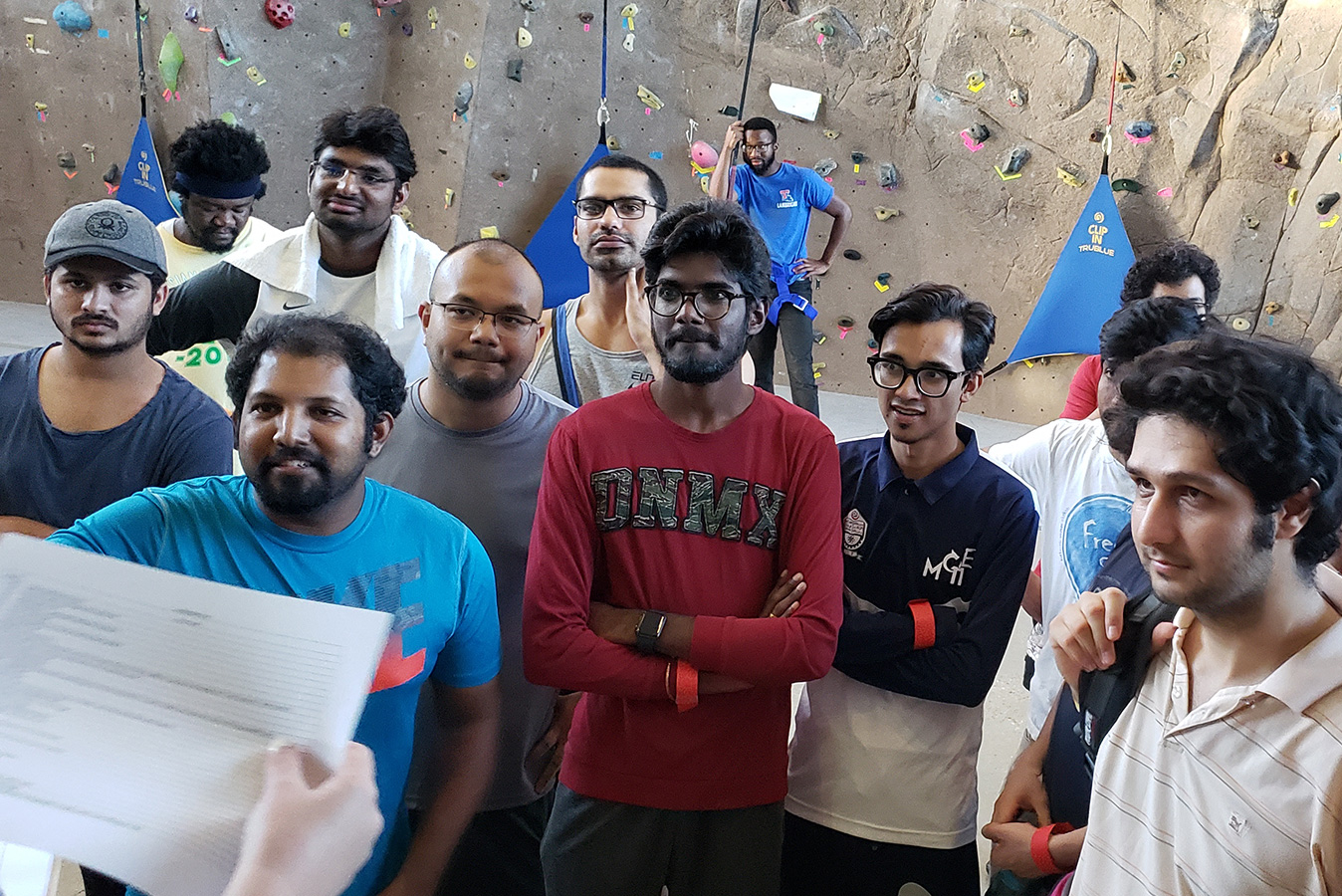 Graduate students gathered in front of a rock climbing wall